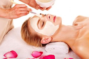 15232721 - woman with clay facial mask with rose petal. isolated.