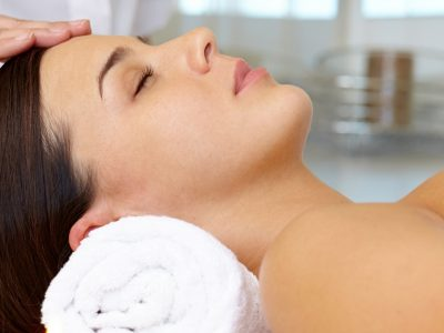 Portrait of young female enjoying the procedure of facial massage